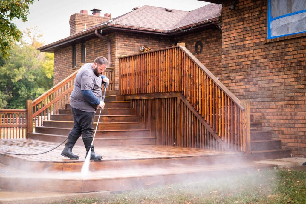 Technician spraying a wood sealant on a deck