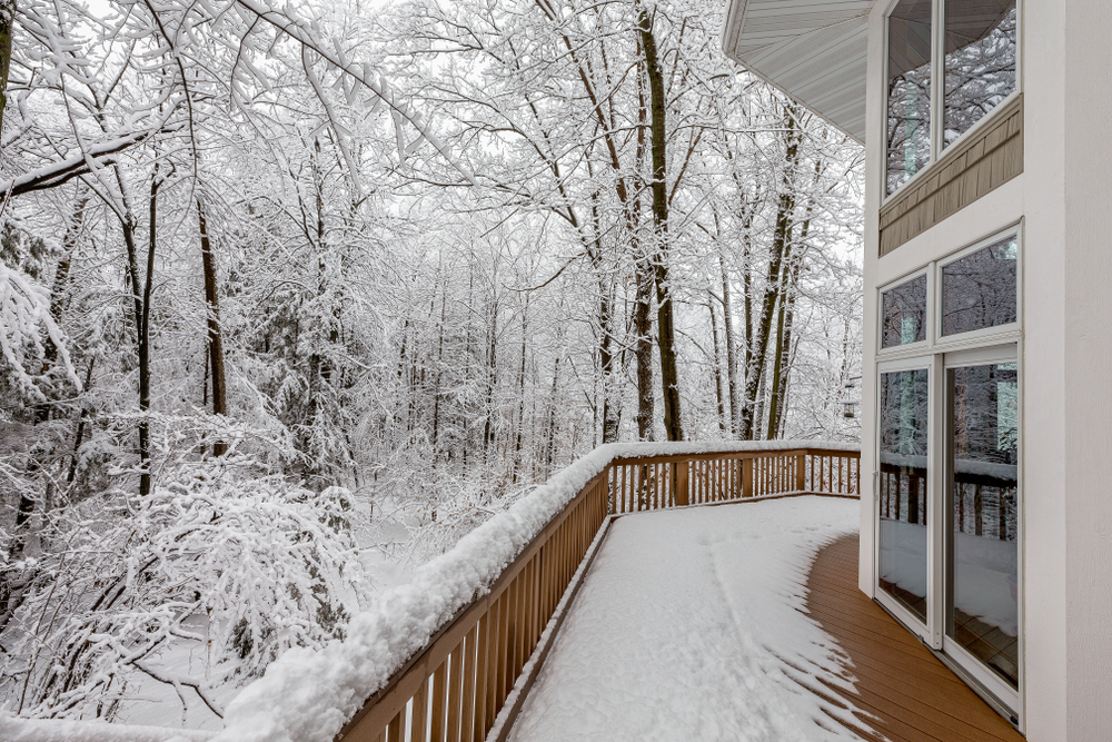 Back wooden deck covered partially in snow