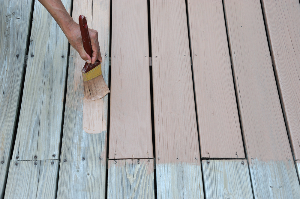 Homeowner painting a wood deck with a brush